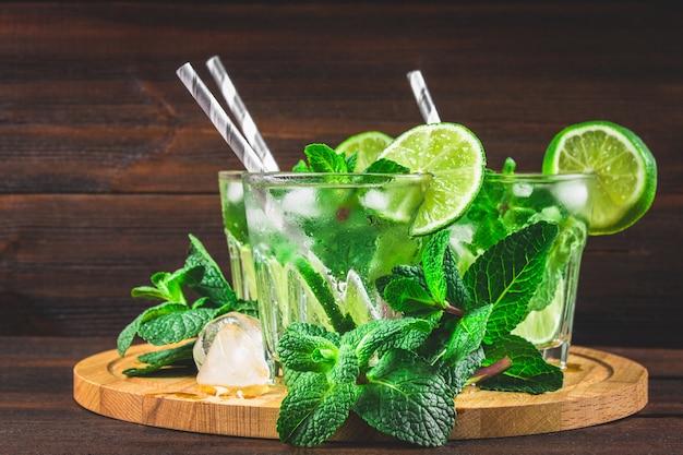 Mojito à la menthe et citron vert dans un verre et un pichet sur le sanglier rond