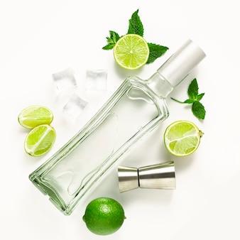 Mojito, à plat avec une bouteille de rhum, citrons verts et menthe sur fond blanc. cocktail mojito à l'alcool
