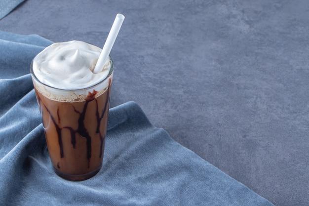 Moka au chocolat dans un verre sur morceau de tissu, sur fond bleu.