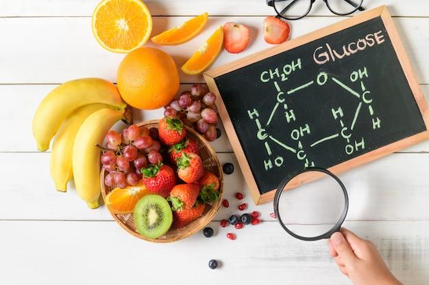 Molécule de glucose sur tableau noir avec salade de fruits frais