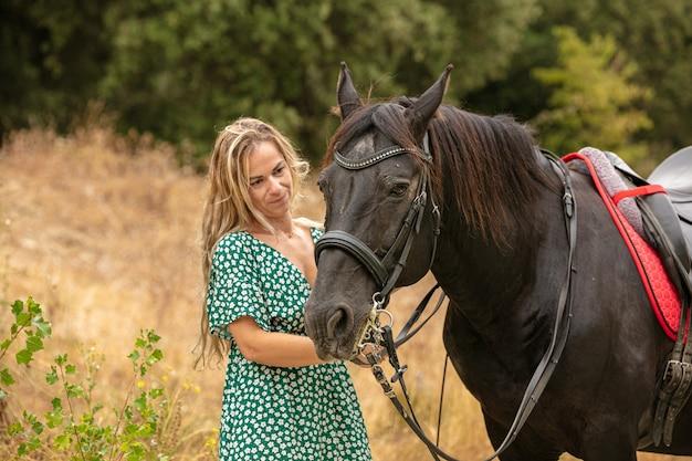 Moment d'amitié entre une femme en robe et un cheval noir en pleine nature
