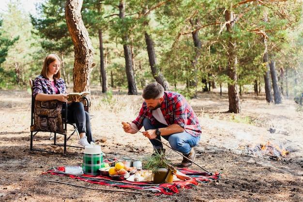 Moment de couple en camping et en préparant la nourriture