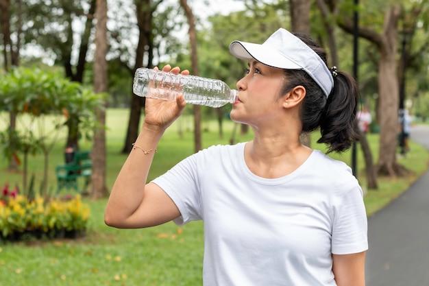 Moment de détente asiat souriant senior femme buvant de l'eau douce en été au parc.