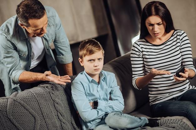 Moment éducatif. agréables jeunes parents réunis autour de leur fils et lui expliquant les raisons de lui retirer son téléphone alors que le garçon a l'air blessé et indigné