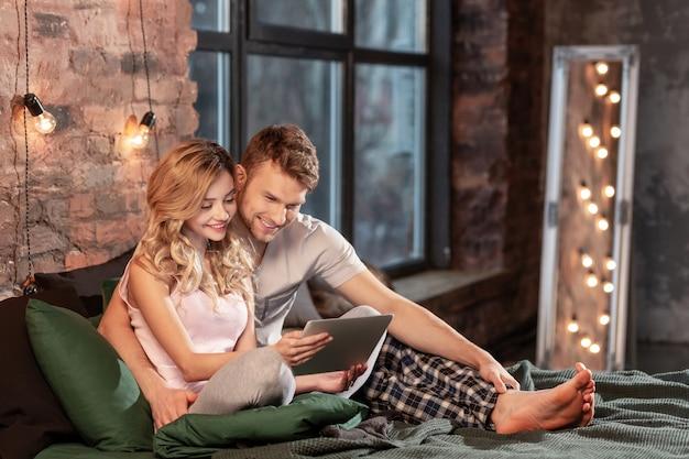 Moment heureux. un couple rayonnant passe un moment agréable et confortable ensemble dans la chambre tout en regardant un film sur une tablette
