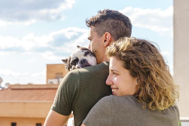 Moment intime d'un jeune couple embrassant un chien à l'extérieur. vue latérale horizontale du couple aimant son chien.