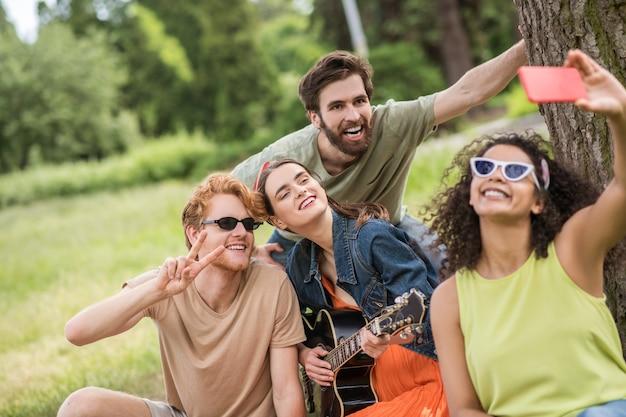 Moment joyeux. jeunes gars et filles heureux et énergiques montrant un signe de liberté prenant un selfie sur un smartphone au pique-nique