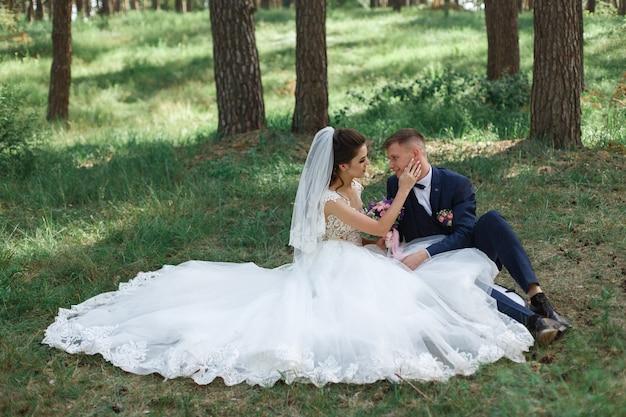 Moment de mariage romantique. heureux jeune couple de mariage étreindre à l'extérieur dans le parc verdoyant. portrait en plein air de beaux jeunes mariés.