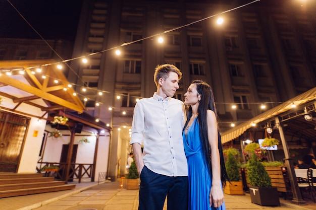 Moment romantique en plein air dans la ville. un rendez-vous romantique. couple d'amoureux sur la ville de nuit. histoire d'amour dans le style de la rue. passion couple amoureux se dresse contre les lumières de la ville de nuit