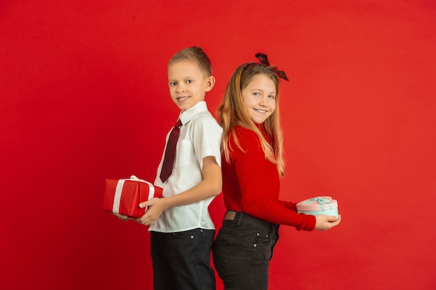 Moment surprenant. célébration de la saint-valentin, enfants caucasiens heureux et mignons isolés sur fond de studio rouge. concept d'émotions humaines, expression faciale, amour, relations, vacances romantiques.