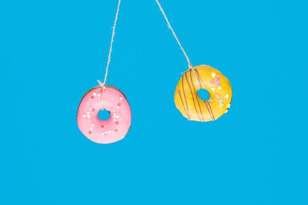 Moment et temps, concept de collision avec deux beignets sur fond bleu.