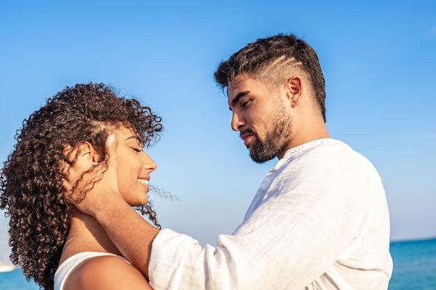 Moment de tendresse entre jeune couple multiracial d'amoureux heureux qui se regardent dans les yeux