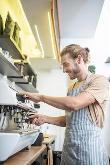 Moment de travail. jeune adulte homme séduisant dans un tablier occupé près de machine à café dans un café de bonne humeur