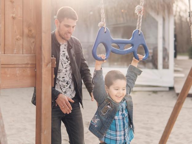 Moments heureux enfant et père sur le terrain de jeu