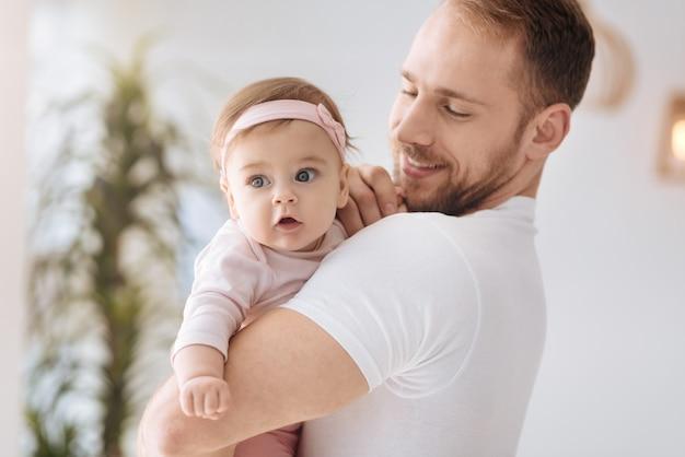 Moments heureux. mignonne petite fille curieuse couchée dans les mains du jeune père et regardant ailleurs tout en exprimant son intérêt