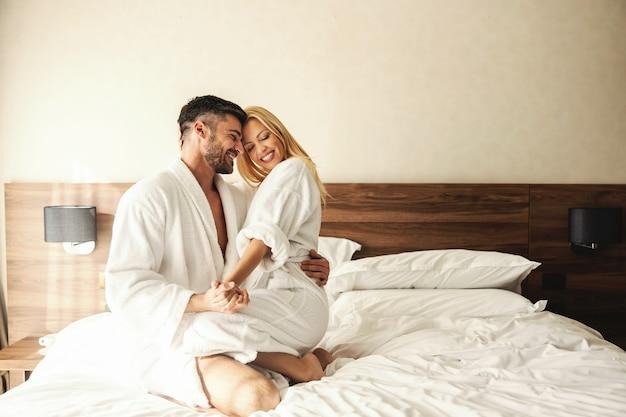 Des moments intimes pleins d'amour et de passion à retenir. heureux couple riant pendant un séjour de vacances dans une chambre d'hôtel. belle blonde assise sur les genoux de son mari bien-aimé, lune de miel, saint-valentin