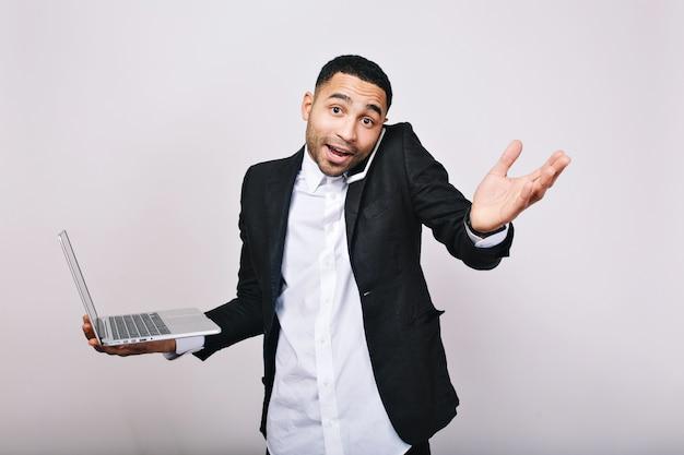 Moments occupés au travail, succès dans la carrière du beau jeune homme en chemise blanche, veste noire tenant un ordinateur portable, parlant au téléphone. homme d'affaires élégant, employé de bureau.