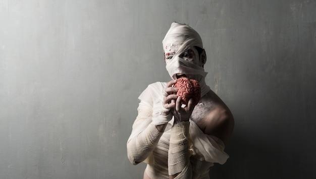 Momie terrorifique manger un cerveau sur fond de mur texturé. vacances d'halloween