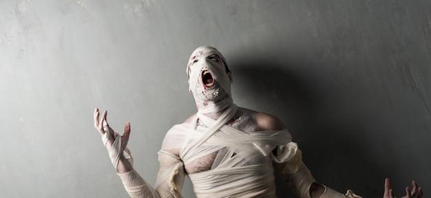 Momie terroriste hurlant sur fond de mur texturé. vacances d'halloween