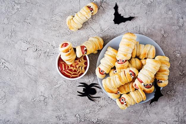 Momies de saucisse effrayantes dans la pâte avec des yeux drôles sur la table. décoration drôle. nourriture d'halloween. vue de dessus. mise à plat