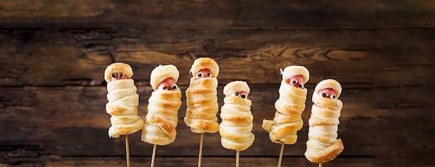 Momies de saucisse effrayantes dans la pâte avec des yeux drôles sur la table. nourriture d'halloween. vue de dessus. mise à plat
