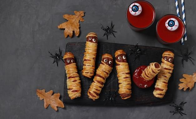 Momies de saucisses effrayantes, jus de tomate et sauce pour la fête d'halloween sur planche de bois foncé. vue de dessus. espace de copie.