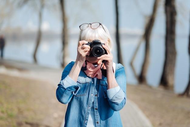 Mon activité préférée. femme mûre inspirée à prendre des photos en marchant dans le parc