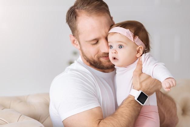 Mon adorable enfant. heureux jeune père paisible assis sur le canapé à la maison et étreignant son nouveau-né tout en exprimant ses soins et son amour