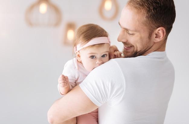 Mon adorable enfant. joyeux père barbu heureux debout à la maison et serrant la petite fille tout en exprimant des émotions tendres