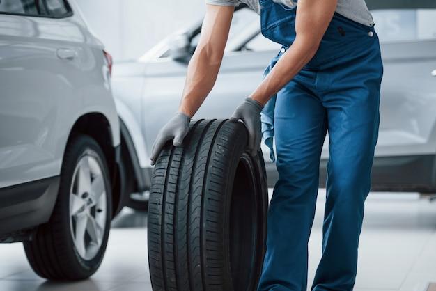 Sur mon chemin. mécanicien tenant un pneu au garage de réparation. remplacement des pneus d'hiver et d'été