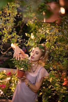 Mon hobby. belle jolie femme prenant soin des fleurs en se tenant debout dans le jardin