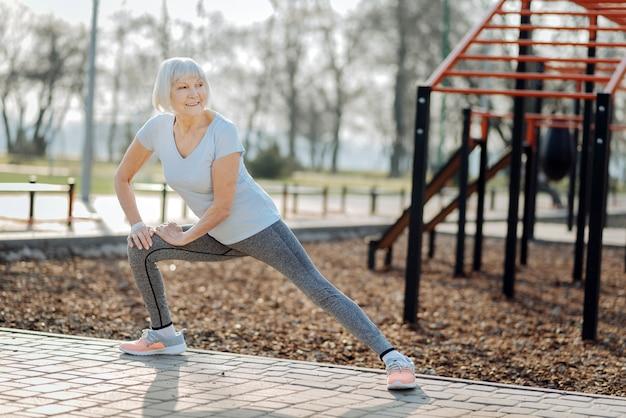 Mon hobby. enthousiaste femme âgée portant des vêtements de sport et exerçant en plein air