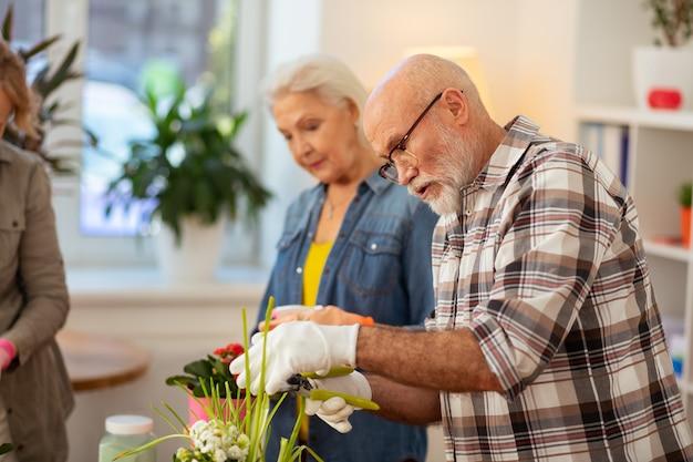 Mon hobby. homme d'âge barbu regardant la fleur tout en étant engagé dans le jardinage