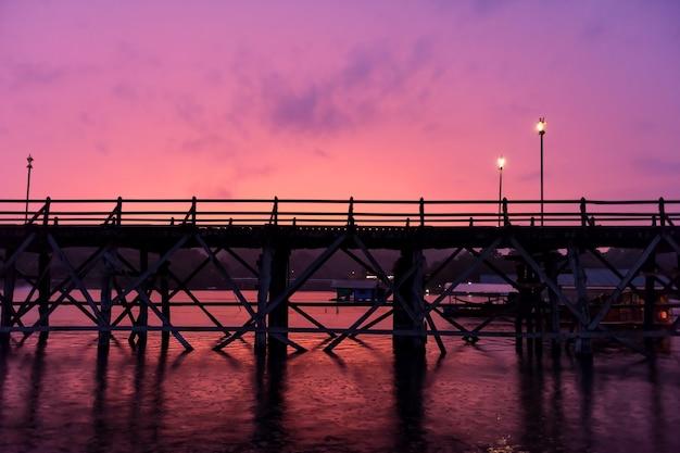 Mon pont en bois et radeau flottant avec de fortes pluies sur la rivière songkalia avec ciel crépusculaire au crépuscule à sangkhlaburi, kanchanaburi, thaïlande. célèbre point de repère de voyage en thaï.
