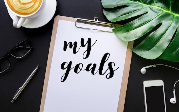 Mon texte d'objectifs avec l'écriture sur du papier à lettres et des accessoires portant sur un tableau noir.