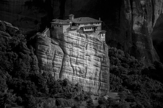 Monastère de la sainte trinité sur un rocher entouré de forêts et de collines sous la lumière du soleil en grèce