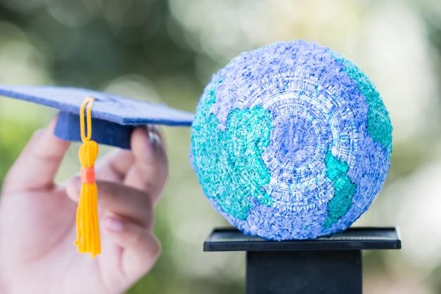 Monde de l'éducation ou chapeau de remise des diplômes sur les mains avec le globe terrestre en papier mâché