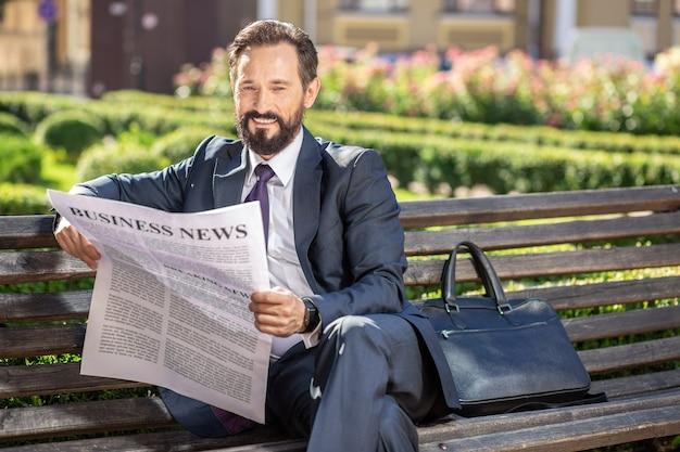 Monde de l'entreprise. agréable homme d'affaires ravi assis sur le banc et lisant un journal d'affaires