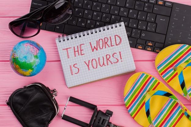 Le monde est à vous sur un ordinateur portable avec un portefeuille de lunettes d'accessoires de voyage pour femme et des tongs sur fond de table rose. globe et clavier noir.