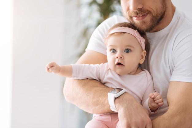 Monde intéressant autour de moi. surpris surpris bébé fille impliquée couché dans les mains du père et regarde ailleurs tout en exprimant son intérêt