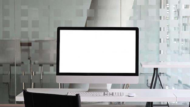 Moniteur à écran blanc blanc mettant sur un bureau de travail blanc avec souris et clavier sans fil sur un bureau moderne.