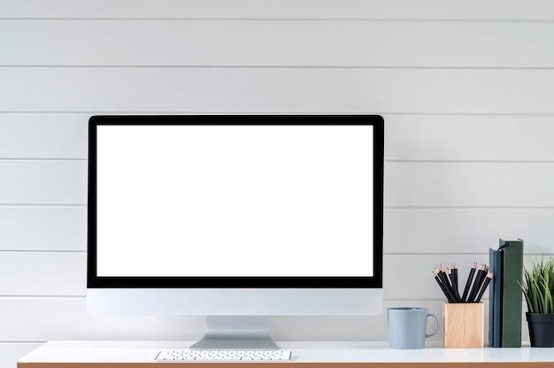 Moniteur d'ordinateur à écran blanc vierge et fournitures sur une table supérieure blanche.