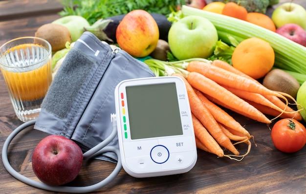 Moniteur de pression artérielle et fruits frais avec des légumes contre la table en bois mode de vie sain et prévention du concept de l'hypertension