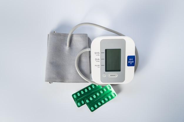 Moniteur de pression artérielle pour prendre la pression artérielle et pilules pour l'abaisser sur fond blanc.