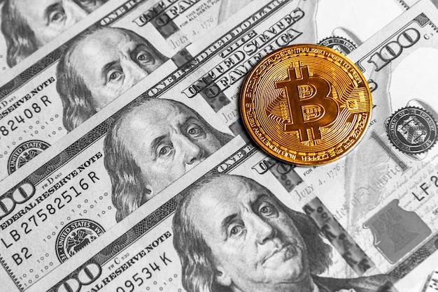 Monnaie crypto bitcoin d'or sur les dollars américains. gros plan sur la crypto-monnaie numérique. echange, affaires, commercial. profitez de l'extraction de devises cryptées. mineur avec des dollars et une pièce d'or bitcoin.