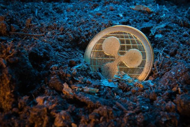 Monnaie crypto minière - ripple coin, pièce d'argent en ligne dans le sol de terre.