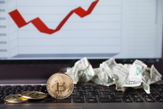Monnaie crypto. pièces d'or bitcoin et dollars froissés sur clavier d'ordinateur portable