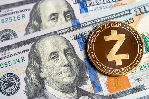 Monnaie crypto zcash d'or sur les dollars américains. gros plan sur la crypto-monnaie numérique. echange, affaires, commercial. profitez de l'extraction de devises cryptées. mineur avec des dollars et une pièce d'or zcash.