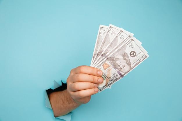 Monnaie dollar dans la main. close-up hand holding billets en dollars à travers le trou dans du papier bleu
