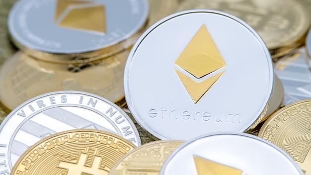 Monnaie ethereum argent métal physique sur d'autres pièces. argent internet virtuel dans le monde entier. cyberespace numérique etherum, crypto-monnaie eth. bon investissement futur paiement en ligne